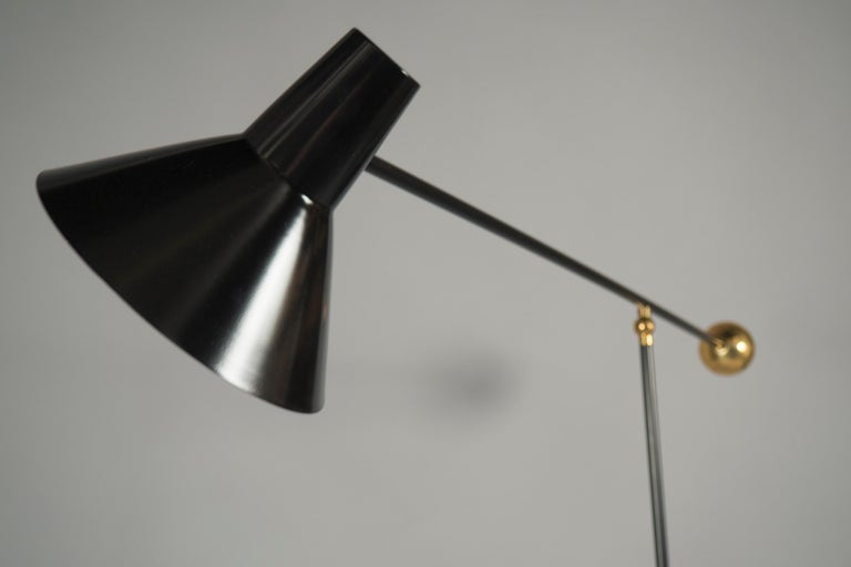 "Black painted and polished brass floor lamp, featuring a conical shade balanced by a counterweight.   Size is adjustable: Height 61-88"", width 22"", depth 18-52""."