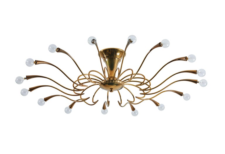 Two flush mount chandeliers by Oscar Torlasco. Designed and manufactured in Italy, circa 1950s. Brass. Rewired for U.S. junction boxes. Takes sixteen E27 European candelabra 25w maximum bulbs. Bulbs provided as a onetime courtesy. Priced and sold