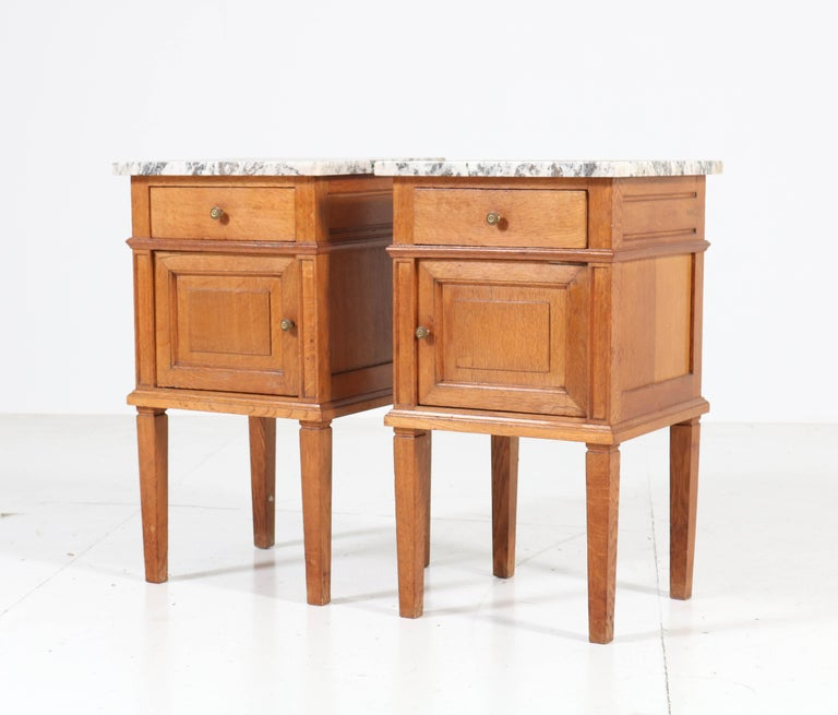 Nice pair of Art Deco nightstands or bedside tables. Striking French design from the 1930s. Solid oak with original brass knobs. Original marble tops. In good original condition with minor wear consistent with age and use, preserving a