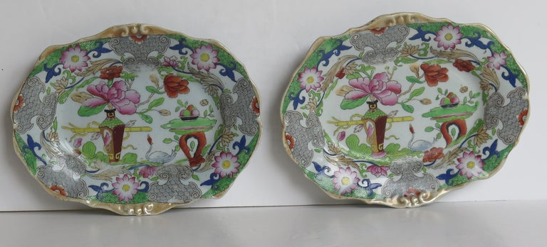 These are a good pair of hand-painted Mason's ironstone small oval dishes, in the table and flower pot pattern, from their earliest George IIIrd period, circa 1818.  These are a well potted pair of small shaped oval moulded edge dishes.  Both
