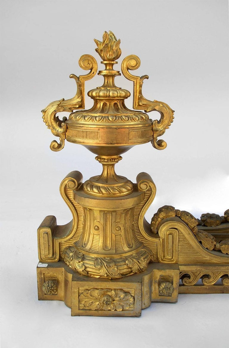 Large pair of chiseled and gilt bronze fire dogs, Louis XVI style. The upright, adorned with stylized waves frieze, is linked to the front part by a volute with acorns and oak leaves. The front part is in cassolette-shape topped by a torch and its