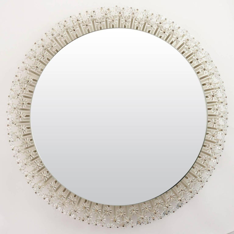 One of two large wall mirrors with illuminated background by Emil Stejnar for Rupert Nikoll, Vienna, Austria, manufactured in midcentury. A round mirror is surrounded by hundreds of glass flowers. This kind of mirror is available in different sizes