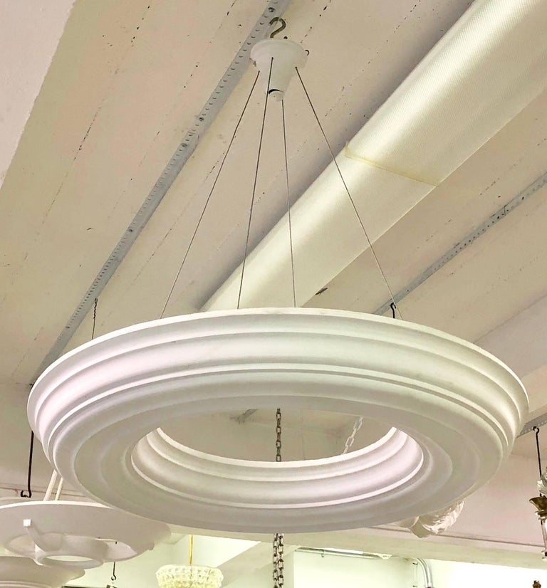 Pair of elegant French late Art Deco style plaster chandeliers in the modern neoclassical tradition in the form of an open ring. Lighting sockets are contained in the sophet that shoot light upward.   Can be wired for four to eight Edison sockets or