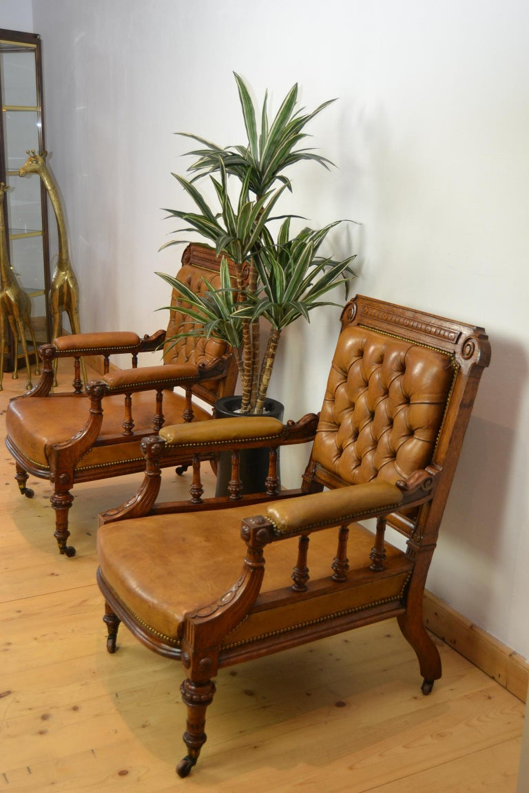 Great looking Antique Library Chairs, Armchairs, Lobby Chairs. These two Imposing English Chairs with a deep seat ,  date from the late 19th century. They have a wooden frame and are upholstered in leather. The back of the chairs have a buttoned