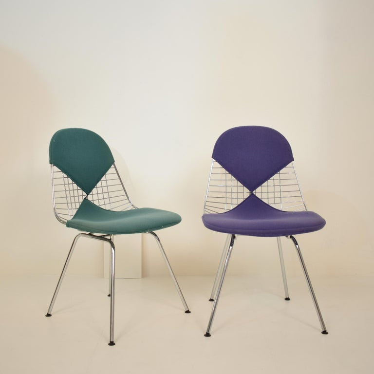 Set of two DKX-2 wire bikini shell chairs on X-bases with two different fabric covers designed by Charles and Ray Eames for Herman Miller.  They are in beautiful vintage condition. The green and the purple bikini covers have been cleaned but have