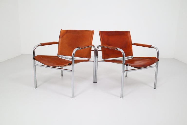 Set of two midcentury tubular chrome arm chairs with patinated cognac leather. An admirable patina is visible on the natural leather, which creates a vibrant surface and stunning color.