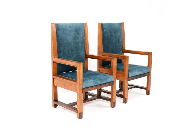 Magnificent and rare pair of two Art Deco Haagse School armchairs. Design by Henk Wouda for H. Pander & Zonen. Striking Dutch design from the 1920s. Solid oak with solid macassar ebony lining. Re-upholstered with a petrol blue velvet