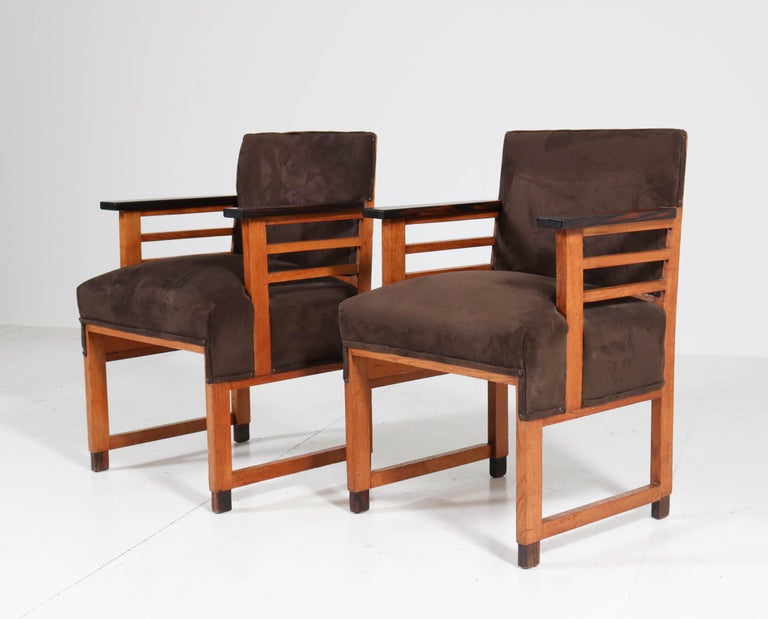 Wonderful and rare pair of Art Deco Haagse school armchairs. Design by t Woonhuys Amsterdam. triking Dutch design from the 1920s. Solid oak with ebony Macassar lining. Re-upholstered with brown fabric. In very good original condition with minor