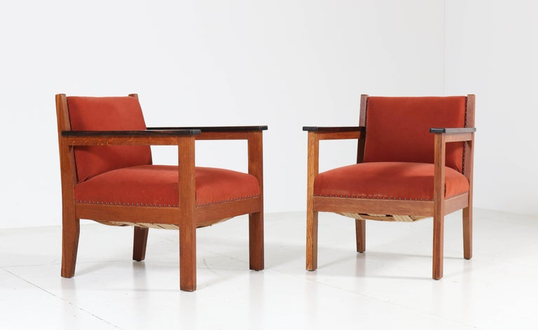 Wonderful pair of Art Deco Haagse School lounge chairs. Striking Dutch design from the twenties. Solid oak with original solid ebony macassar armrests. Re-upholstered by the former owner. In good original condition with minor wear consistent