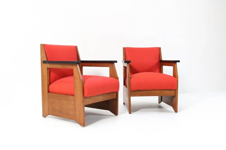 Magnificent pair of Art Deco Haagse School lounge chairs. Design by Hendrik Wouda for H. Pander & Zonen. Striking Dutch design from the 1920s. Solid oak with black lacquered armrests. Re-upholstered with cotton fabric. Marked with original