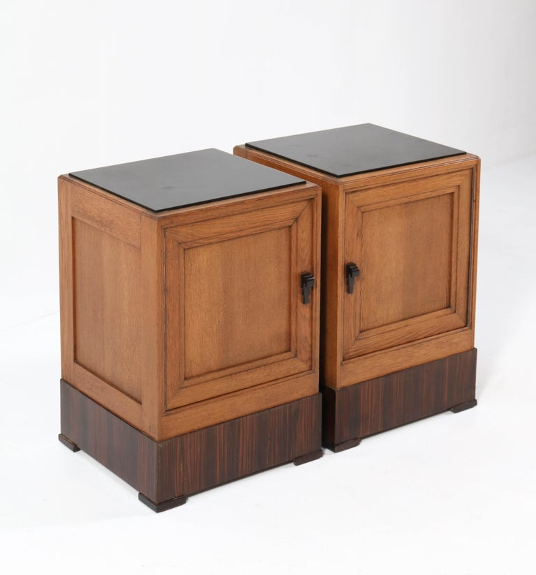Magnificent and rare pair of Art Deco Haagse School nightstands or bedside tables. Striking Dutch design from the 1920s. Solid oak with solid Macassar ebony handles. Original black granite tops. This pair of high quality is in very good