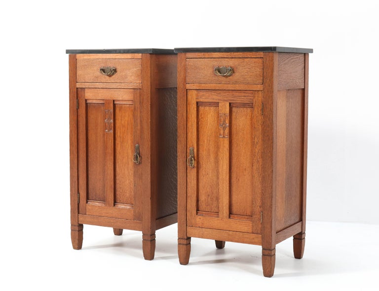 Magnificent and rare pair of Arts & Crafts Art Nouveau nightstands. Design by H. Pander & Zonen. Striking Dutch design from the 1900s. Solid oak with black marble tops. Original brass handles on doors and drawers. Marked with original