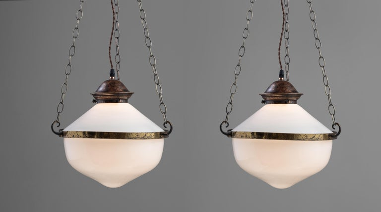 Two part opaline suspension lamps, England circa 1930  Two opaline shades with brass central band and chains running up to a brass 4-way hook.