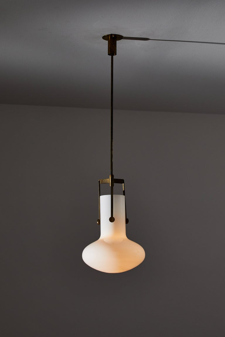 Two pendants by Venini. Designed and manufactured in Italy, circa 1960s. Opaline glass, brass. Wired for U.S. standards. Custom brass ceiling plates. We recommend one E26 75w maximum bulb per fixture. Bulbs provided as a one time courtesy. Overall