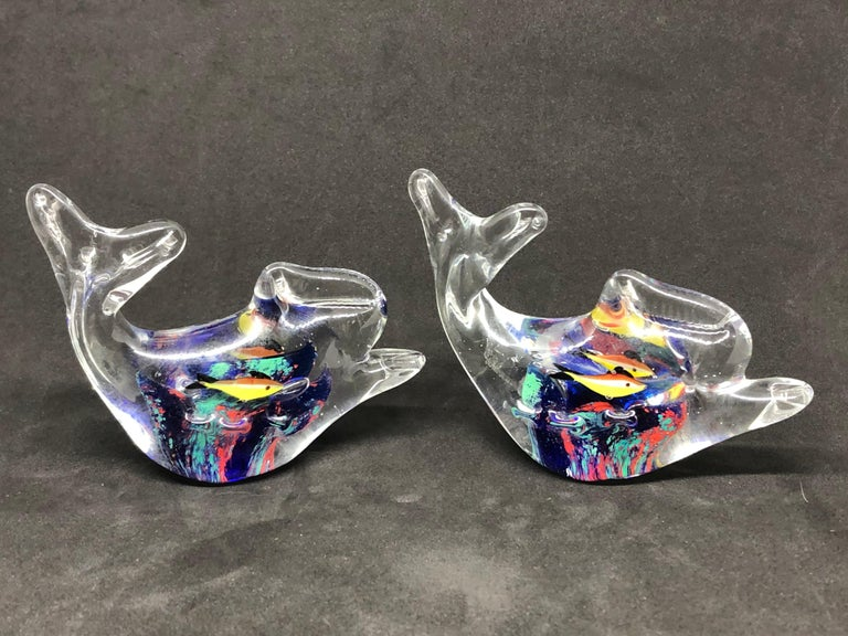 Two beautiful Murano hand blown aquarium Italian art glass paper weights. Showing some multicolored fishes and a coral reef inside a clear glass fish. A beautiful nice addition to your desktop or as a decorative piece in every room.