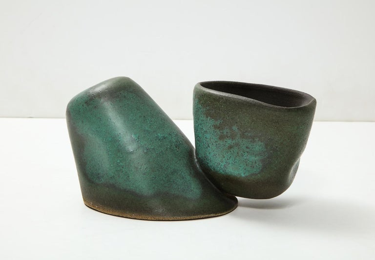 Hand molded assembly, bowl floating alongside leaning cone. Smooth naturalistic indentations throughout, in green glazes. Artist-signed to underside.