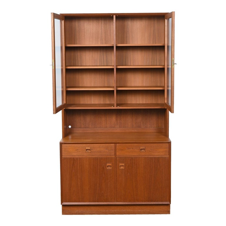 Exceptional two-piece bookcase cabinet hutch with carved teak pulls by Brouer Møbelfabrik. The craftsmanship is exquisite and the original owner treated this piece like a jewel. It is in excellent overall condition and only required moderate
