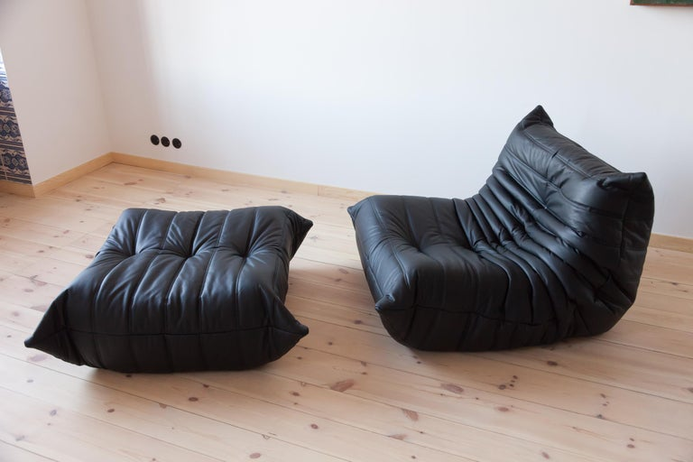 This Togo living room set was designed by Michel Ducaroy in 1974 and manufactured by Ligne Roset in France. It has been reupholstered in black high quality leather, and is made up of the following pieces, each with the original Ligne Roset logo and