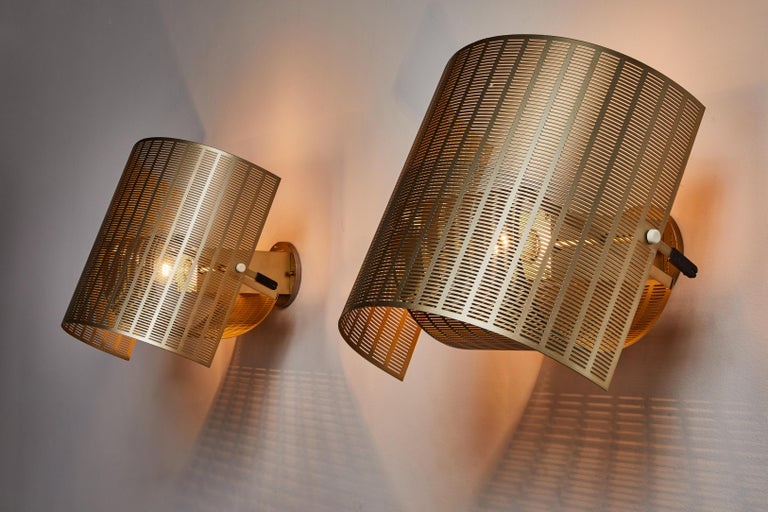 Two rare gold colored shogun sconces by Mario Botta. Designed and manufactured in Italy, 1985. Rewired for U.S. standards. Gold enameled metal. Custom brass backplates. Sconces articulate in an up/down position. We recommend one E27 60w maximum bulb
