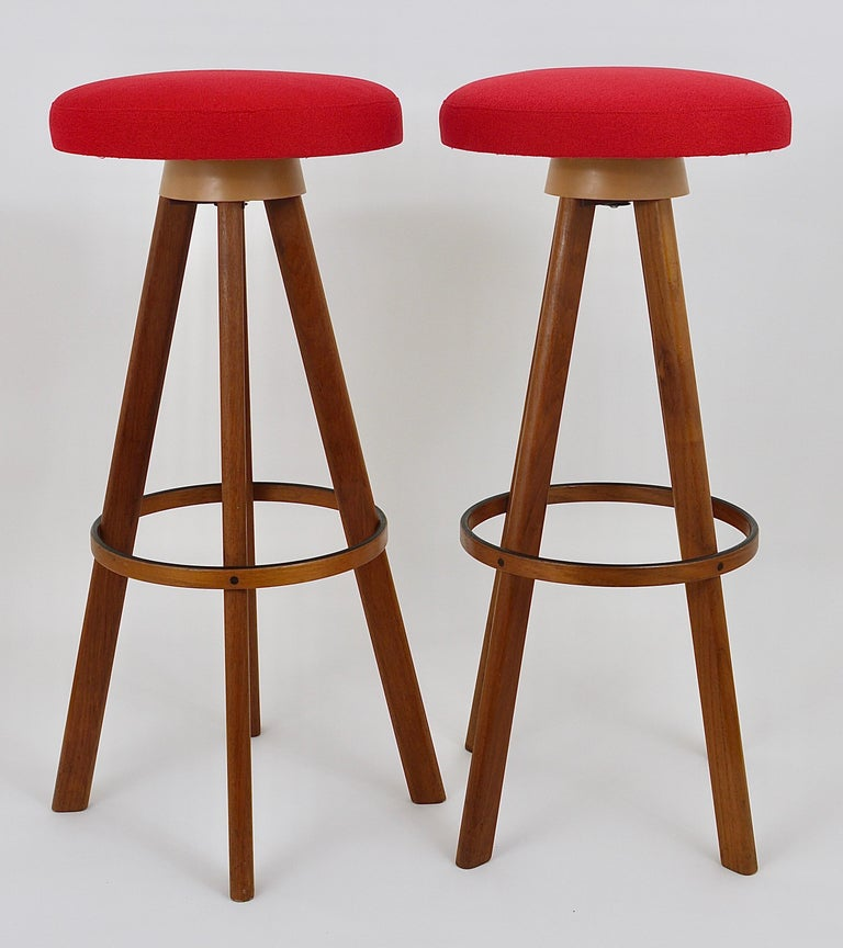 Up to two identical Danish midcentury barstools or counter stools, designed in the 1960s by Hans Olsen executed by Frem Rojle in Denmark. These great looking stools are made of solid teakwood. The swiveling round seats have a red fabric upholstery.