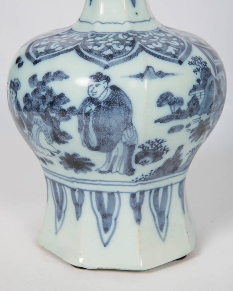 This matched pair of blue and white delft vases dates to the late 17th century. Each vase is decorated with figures and floral patterns. They share the same style of composition. Each long neck is painted with a flower branch and banana leaves