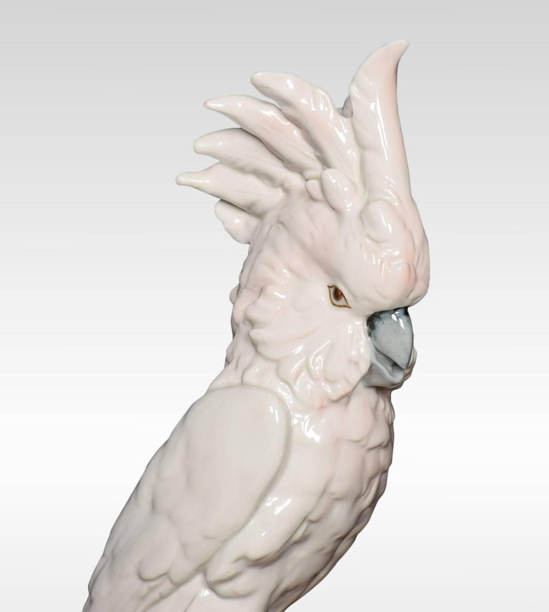 A mid-20th century Royal Dux porcelain figure of a cockatoo. The cockatoo is displaying it's crest and is sitting on a branch with flowers underneath. Together with another much smaller cockatoo sitting on a branch. Bottoms marked with all the