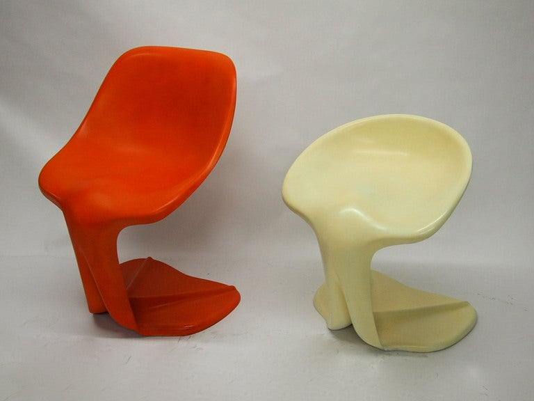 """Pair of """"his and hers"""" chairs designed in 1970 by Jean Dudon and made of molded fiberglass with a gel coated  finish one in orange the other in off-white Documented in"""
