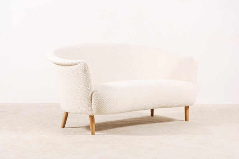 Two-seat curved sofa manufactured in Italy during the 1950s. Lovely shape and curves. Very comfortable seat. Beechwood natural color waxed feet.  This sofa has been fully restored and newly upholstered in the traditional way by the best French