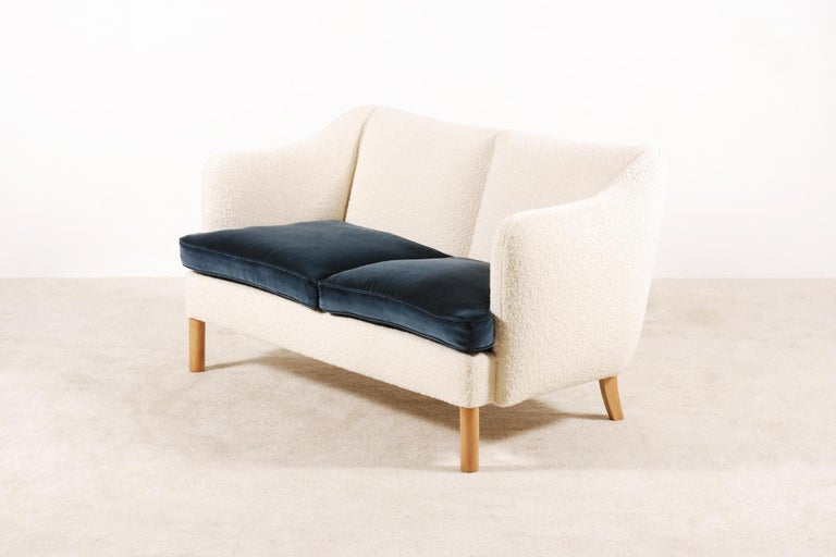 Beautiful two-seat curved sofa manufactured in the 1950s. Lovely shape and curves. Very comfortable seat with two feather cushions covered of blue Kvadrat velvet.  Perfect condition, fully and newly upholstered with a high quality French wool