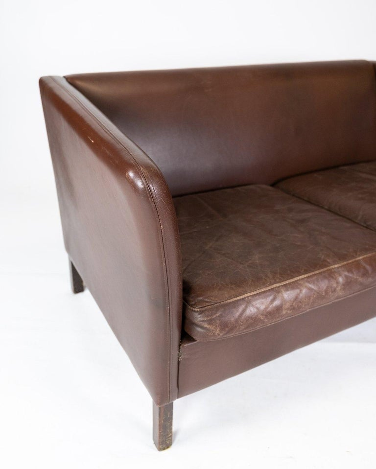 Two seater sofa upholstered with dark brown leather of Danish design manufactured by Stouby Furniture in the 1960s. The sofa is in great vintage condition.