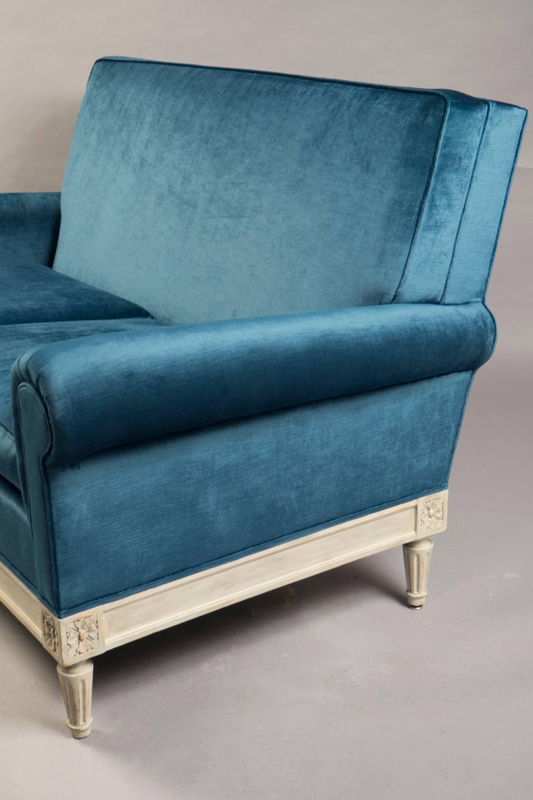 """Two-seat sofa with a white-washed wooden base with classical rosette carvings and tapered legs, supporting an over-upholstered seat, back and sides, covered in rose Cumming's antique blue velvet.  Measures: Height back 33.5"""", width 54"""", depth"""