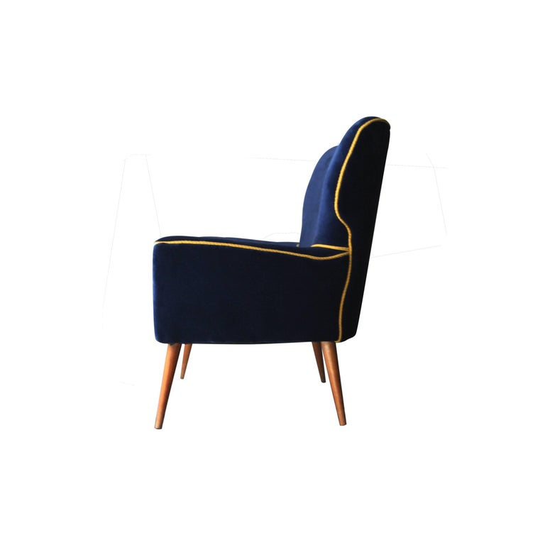 Two-seat sofa with solid wood structure, blue velvet upholstery and yellow piping. Conic legs made of birchwood.