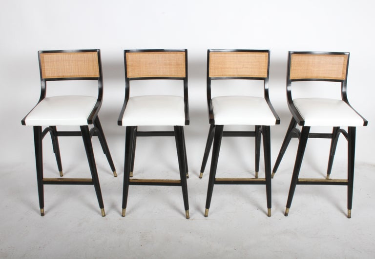 I have eight matching bar stools, selling them in sets of four. Beautiful Mid-Century Modern bar stools in the style of Edward Wormley for Dunbar with caned backs, black lacquered frames, brass sabots, white vinyl seats and brass covered footrest.