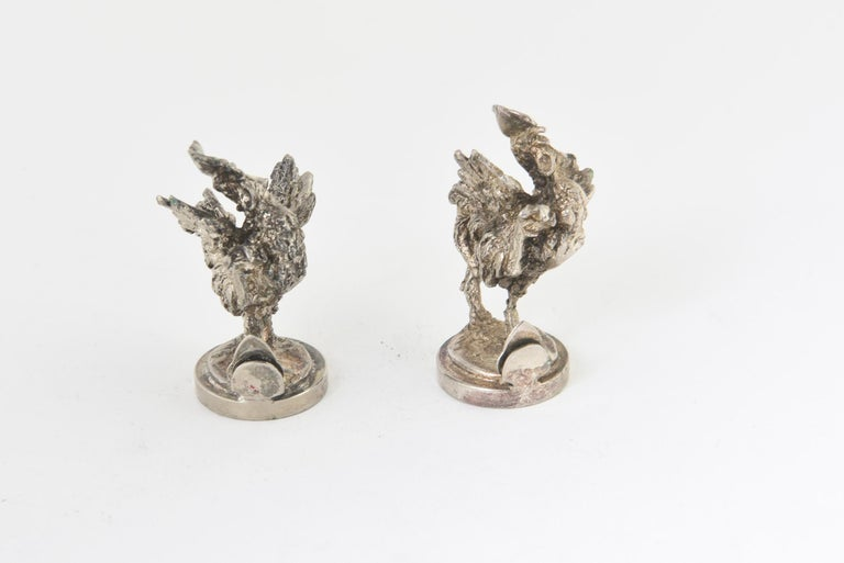 Highly stylized pair of vintage silver plate rooster menus, place cards, or card holders. Great detail to their facial expressions and bodies. There is a clip attached to the base to hold a menu or place card.