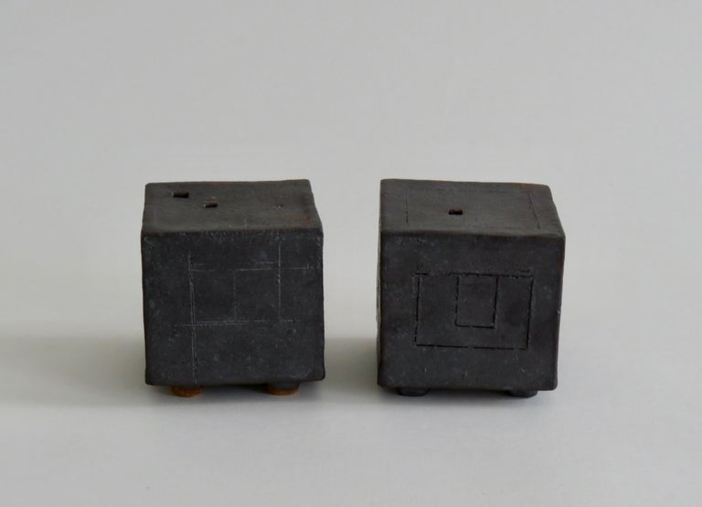 A pair of small 3 inch cube box or bud vase to hold your thoughts or a tiny flower. Hand carved line-drawn geometric designs, each side is different. The tops contain rectangular openings. They each stand on their own 4 little feet, adding lightness