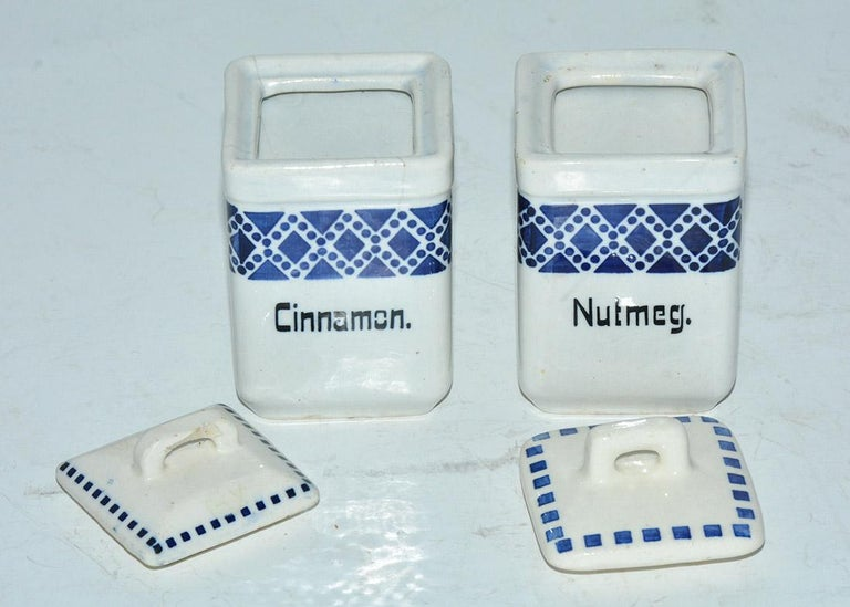 The two square vintage canisters hold nutmeg and cinnamon and have hand-painted designs in blue. Made of pottery. Stamped