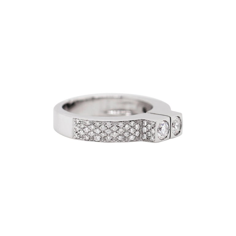 This unique dress ring features two round brilliant cut diamonds weighing approximately 0.20ct each, set beside each other in run over square settings. The two stones are accompanied by pavé set diamond shoulders mounted with a total of 76 round