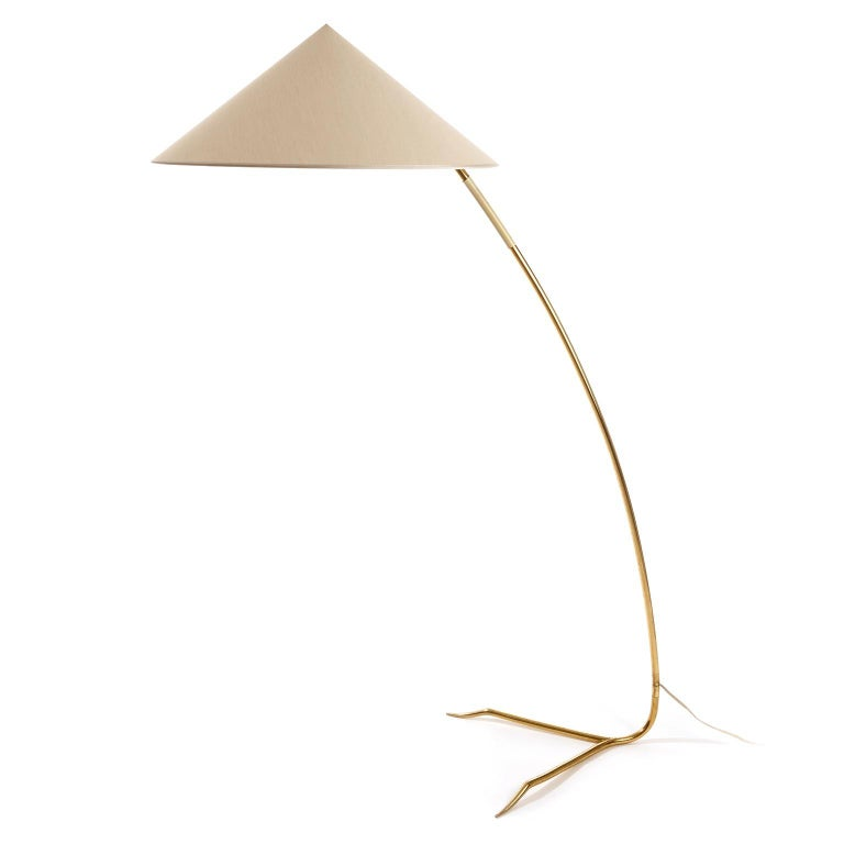 One of two gorgeous and rare floor lights with model name 'Sumatra' by Rupert Nikoll, Austria, manufactured in midcentury, circa 1950s. A cone shaped lamp shade sits on a solid brass stand with a white plastic handle and a straddled base. The