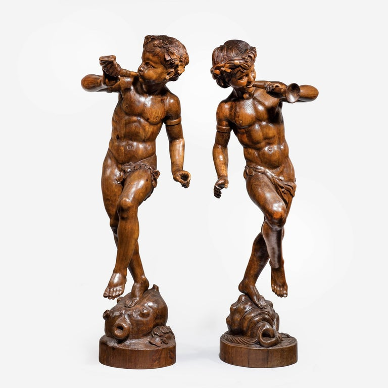 Two superb Italian pine Bacchanalian figures dancing with garlands in their hair, one on a wine skin with a horn, the other on a shell with a trumpet.