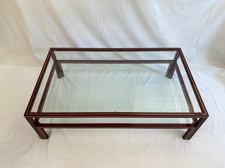 Very nice coffee table with two levels designed by Pierre Vandel, 1970s. The painted metal structure in beautiful red burgundy offers two clear glass trays one of which is beveled. The table is in very good condition.  Très belle table basse à