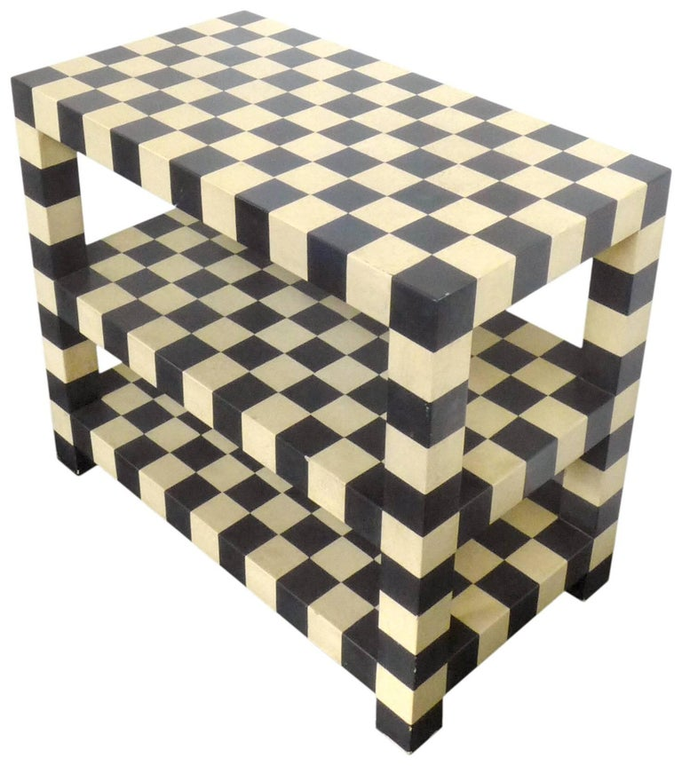 A spectacularly graphic, two-tiered checkerboard table. A strong, architectural form of lacquered wood, in alternating black and warm-white squares. Great scale and proportions. This table could function well as either a small console, occasional or
