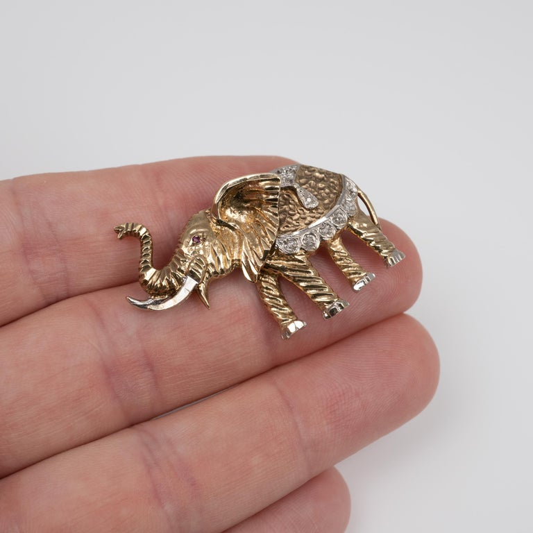 A fabulous vintage diamond and ruby yellow and white gold elephant brooch.  The two-tone gold elephant with trunk up is nicely crafted with a stylish textured pattern. It is set with diamonds and a single ruby to the eye.  The item is fully
