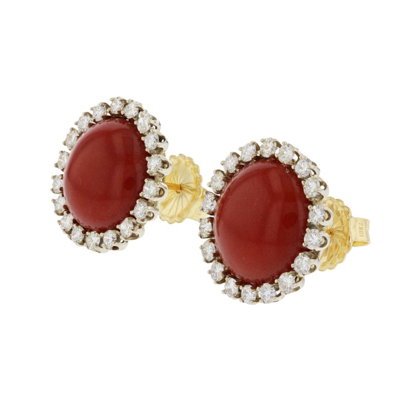 These earrings are set in 18K yellow gold with the diamonds being set in 14K white gold.  The centers are 16mm Oxblood coral cabochons.  Surrounding the coral, are thirty-six (36) round diamonds totaling 2.50 carats; they are G-I in color and