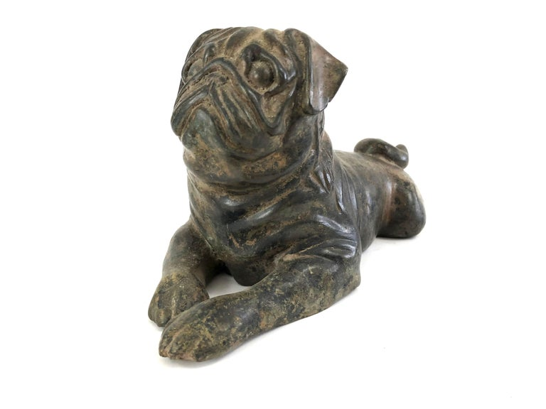 A well modeled and very charming pug in cast iron with traces of worn old gilded surface, lying down with paws in front and tucked in behind, head up with alert expression.  Perfect for pug, dog and animal lovers of all kinds.  Provenance: The