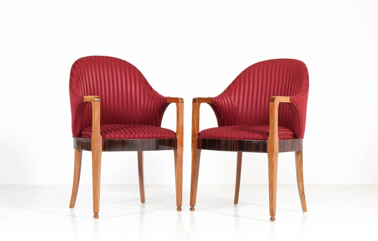 Wonderful pair of Art Deco armchairs. Striking French design from the thirties. Solid walnut with ebony Makassar veneer lining. Re-upholstered with red striped fabric. In good original condition with minor wear consistent with age and
