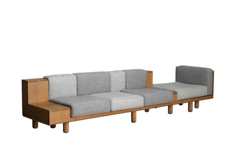 A stretched sofa for large spaces with generous seating for 4. The visually extruded form alternates between solid and soft accommodating different ways of sitting with places to rest your drink or stack some reading.