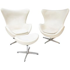 Two White Leather Egg Chairs and Footstool