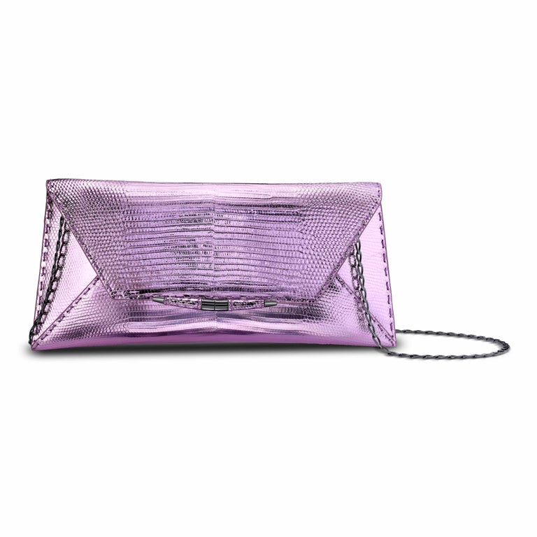The Aimee in Electric Rose Lizard is a clutch designed with a three-quarter front flap, a magnetic snap closure and is finished with our custom Infinity Bar. It fits the large iPhone, has a hidden exterior pocket, an optional gunmetal cross-body