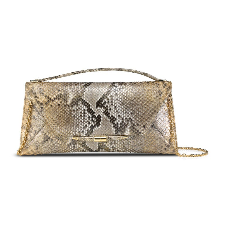 The Aimee clutch large is featured in Metallic Gold Natural Python with gold hardware. The clutch is designed with a top handle, three-quarter front flap, a magnetic snap closure and is finished with our custom Infinity Bar. It fits the large