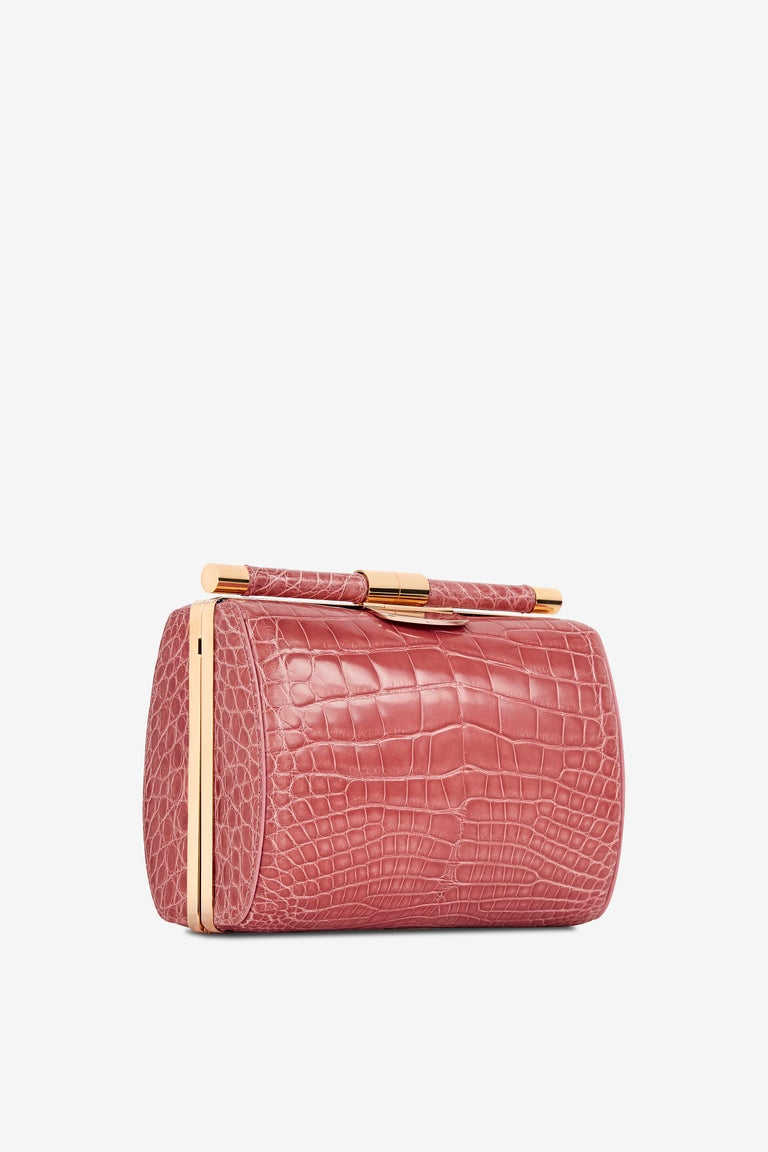The Anjuli Clutch Medium Rose Alligator Rose Gold Hardware is a structured oval clutch, with an optional cross-body chain, and interior pocket. It features our signature slide-lock closure and Thayer blue satin lining.   Size: Medium Hardware: Rose